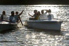Silhouette de jeunes amis dans des canots automobiles Images stock