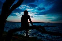 Silhouette des jeunes femmes s'asseyant sur l'arbre au coucher du soleil image stock