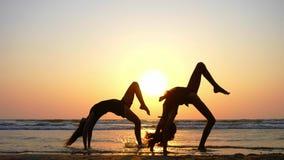 Silhouette des jeunes femmes sportives pratiquant l'élément acrobatique sur la plage banque de vidéos