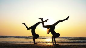 Silhouette des jeunes femmes sportives pratiquant l'élément acrobatique sur la plage clips vidéos