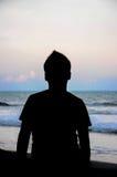 Silhouette des jeunes garçons jouant à la plage pendant le coucher du soleil Photos libres de droits