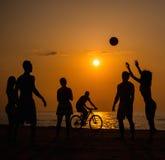 Silhouette des jeunes sur une plage Image stock