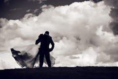Silhouette des ménages mariés sur le fond de nuages Photo libre de droits