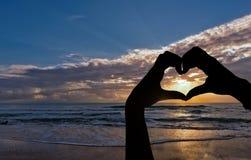 Silhouette des mains avec la forme de coeur par la mer Photos stock