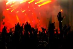 Silhouette des mains dans le ciel sur un concert Photographie stock libre de droits