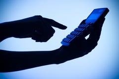 Silhouette des mains de la femme avec la calculatrice images stock