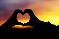 Silhouette des mains en forme de coeur image stock
