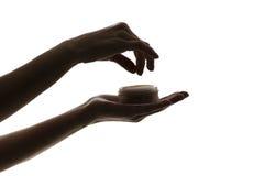 Silhouette des mains femelles tenant la poudre de visage sur le fond blanc Images libres de droits
