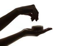 Silhouette des mains femelles tenant la poudre de visage sur le fond blanc Photo libre de droits