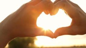 Silhouette des mains sous forme de coeur avec des rayons du coucher de soleil banque de vidéos