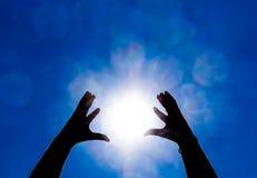 Silhouette des mains sur le fond du soleil et de ciel bleu Des mains sont augmentées jusqu'au soleil Photographie stock libre de droits