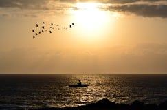 Silhouette des pêcheurs avec son bateau photo stock