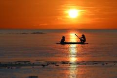 Silhouette des p?cheurs locaux ramant de petits bateaux le long de la c?te par le coucher du soleil rouge de ciel de plage image libre de droits