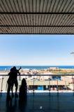 Silhouette des passagers attendant sur la terrasse ouverte dans l'aéroport Images libres de droits