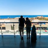 Silhouette des passagers attendant sur la terrasse ouverte dans l'aéroport Photos stock