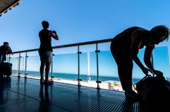 Silhouette des passagers attendant sur la terrasse ouverte dans l'aéroport Photos libres de droits