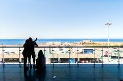 Silhouette des passagers prenant le selfie sur la terrasse ouverte dans l'aéroport Image stock
