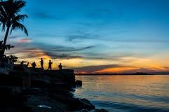 Silhouette des personnes à la plage dans le coucher du soleil Photo stock