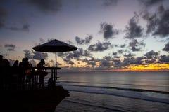 Silhouette des personnes au fond de coucher du soleil de barre photos stock