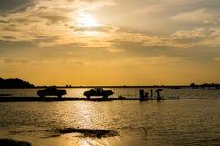 Silhouette des personnes avec la voiture dans le coucher du soleil Images libres de droits