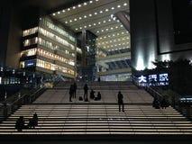 Silhouette des personnes détendant, et attendant, la nuit sur des étapes en dehors de station de train d'Osaka, le Japon Image stock