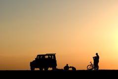 Silhouette des personnes, des voitures et de la bicyclette au coucher du soleil Photographie stock libre de droits