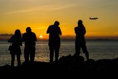Silhouette des personnes et de l'avion pendant le coucher du soleil Photo libre de droits