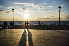 Silhouette des personnes marchant au coucher du soleil par la mer Photographie stock