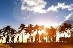 Silhouette des personnes marchant au coucher du soleil sur Waikiki serré Photo libre de droits