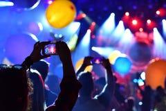 Silhouette des personnes prenant des photos avec les téléphones intelligents à l'escroquerie vivante Images libres de droits