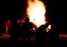 Silhouette des personnes s'asseyant devant un feu de camp pendant la nuit Images stock
