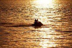 Silhouette des personnes sur le jet-ski Image stock