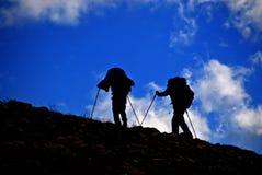 Silhouette des personnes trimardant sur le flanc de montagne Photo stock