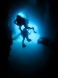Silhouette des plongeurs autonomes dans une caverne sous-marine Photographie stock libre de droits