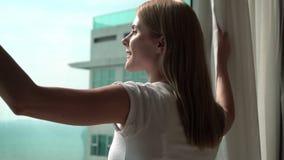 Silhouette des rideaux en dévoilement de jeune femme et regard hors de la fenêtre Appréciant la vue de mer dehors banque de vidéos