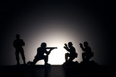 Silhouette des soldats sur un fond foncé image stock
