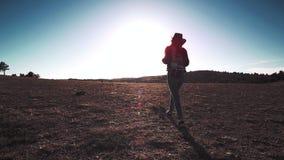Silhouette des sports minces femelles dans le chapeau avec le sac à dos marchant sur le champ au coucher du soleil banque de vidéos