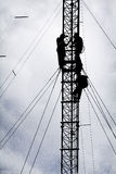 Silhouette des travailleurs réparant la tour de communication Images libres de droits