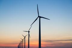 Silhouette des turbines de vent au coucher du soleil Images stock