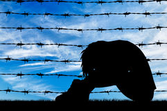 Silhouette Despair refugee woman. Concept of refugee. Silhouette Despair refugee woman near the fence of barbed wire Stock Images
