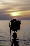 Silhouette of Digital camera beside sea at sunset Stock Image