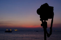 Silhouette of digital camera on tripod with sunset sky at sea bl Stock Photography