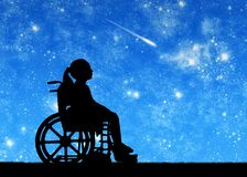 Silhouette of a disabled child girl sitting in a wheelchair looking at the starry sky stock photos