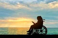 Silhouette of a disabled child girl sitting in a wheelchair reading a book on a sea sunset background. Conceptual image of the life of children with stock photos
