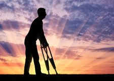 Silhouette of a disabled man with crutches walking against the sunset. The concept of people with disabilities with crutches Royalty Free Stock Image