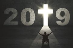 Disabled man with cross symbol and number 2019 royalty free stock images