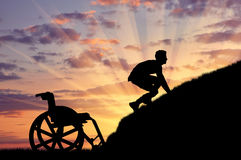 Silhouette of disabled person. Concept of disability and self-motivated. Silhouette of disabled person to climb the hill at sunset Stock Photo