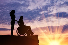 Silhouette of disabled person with a guardian Royalty Free Stock Images