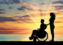 Silhouette of disabled person with a guardian Stock Photography