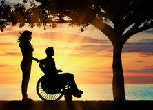 Silhouette of disabled person with a guardian Royalty Free Stock Photography
